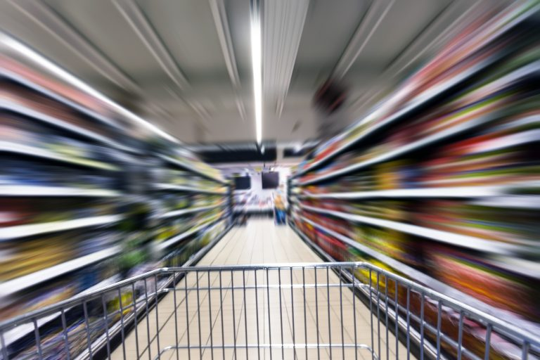 Motion blurred shopping cart in market store